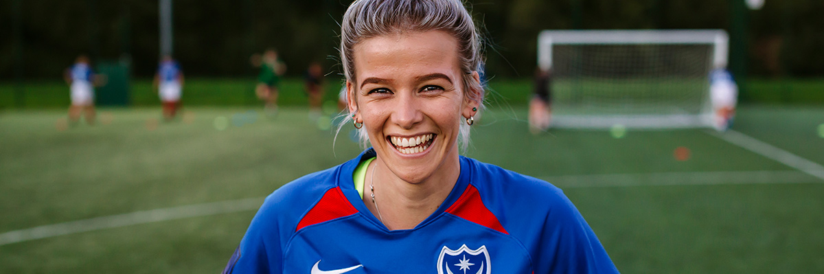 Portsmouth women's football team member wearing their kit and smiling