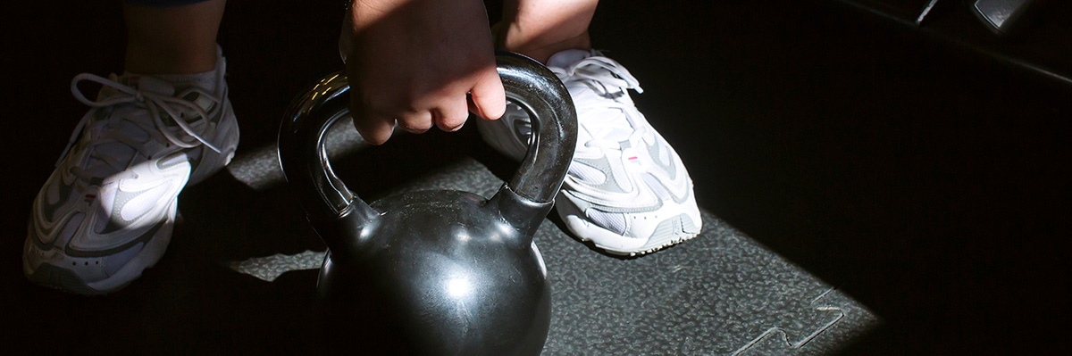Person holding onto a kettlebell on the floor, with white trainers on, partially covered by shadows