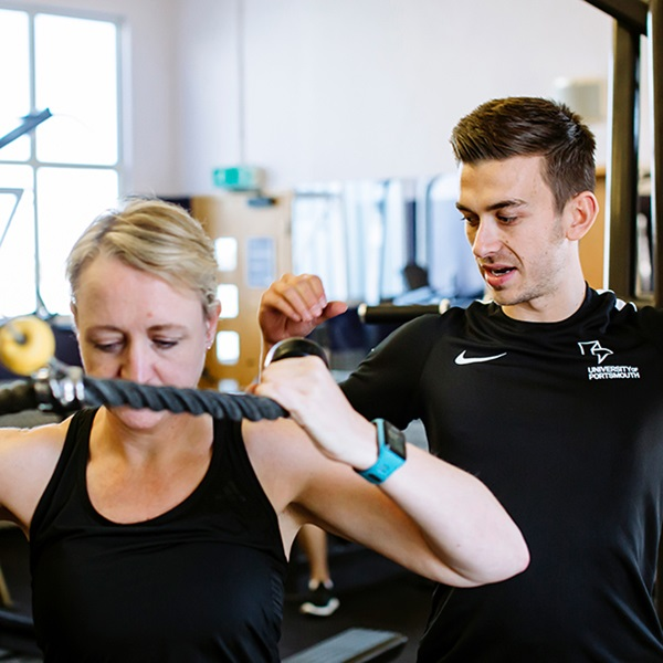 Personal trainer working with woman helping her use the rope on the cable machine