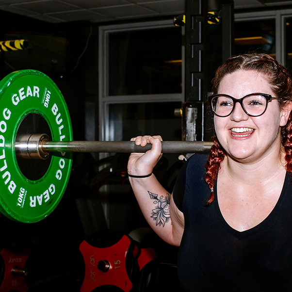 Woman wearing glasses, squatting with barbell with green weights