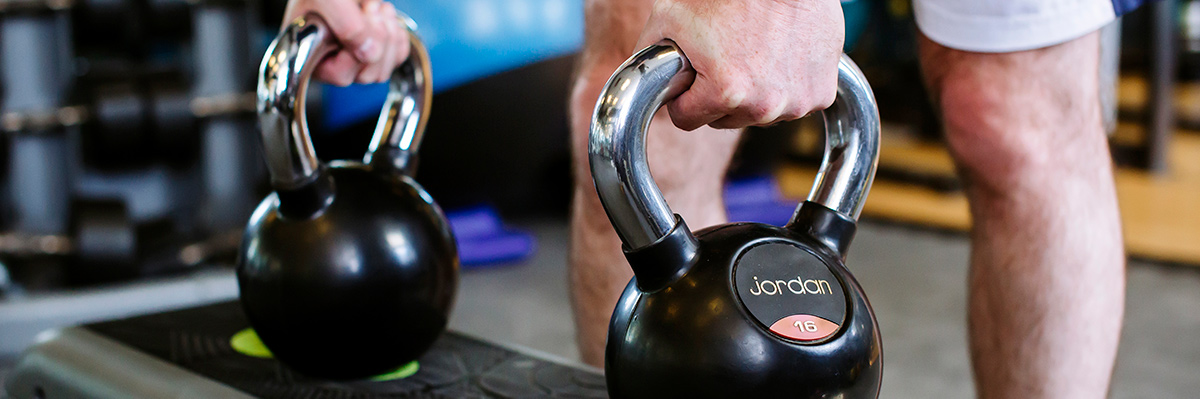 Man holding onto two kettlebells getting ready to lift them off the step