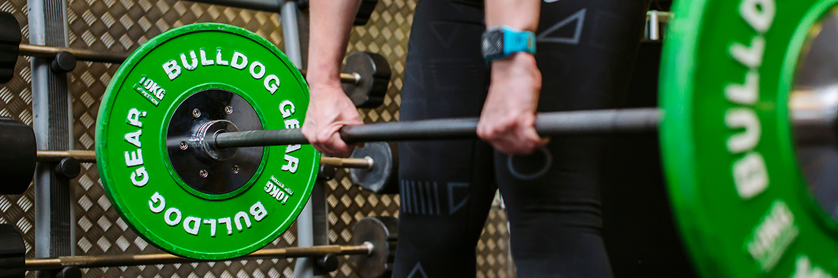 person lifting barbell with green 10kg weights in the gym