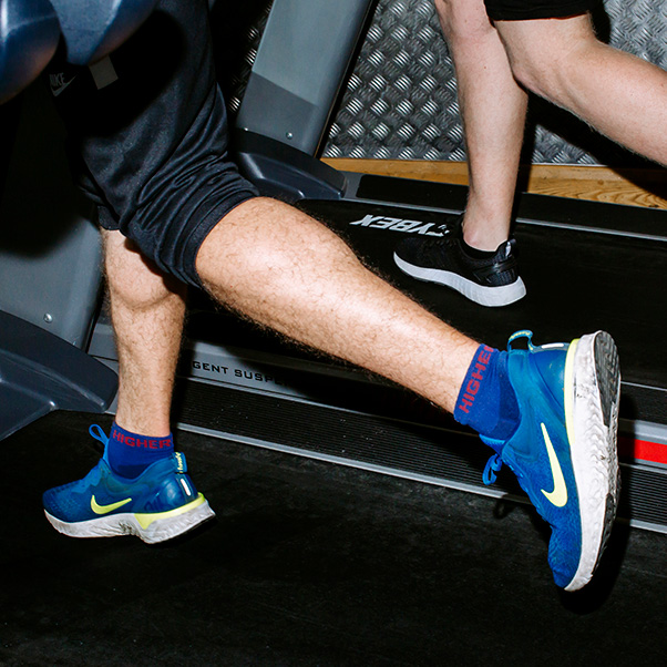 lower half of two people running on treadmills, with blue and black trainers