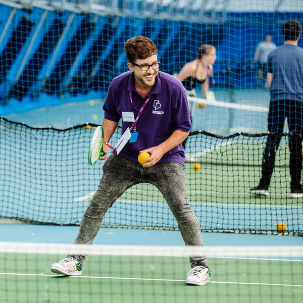 Student ambassador playing tennis with children