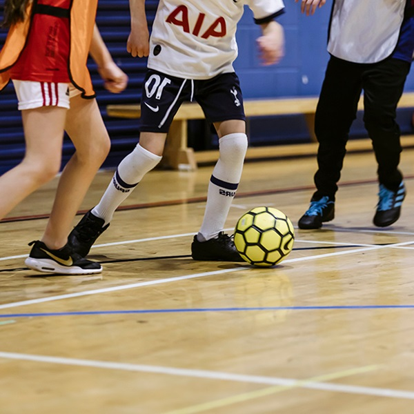 Children playing football, kicking the ball, inside the spinnaker sports centre