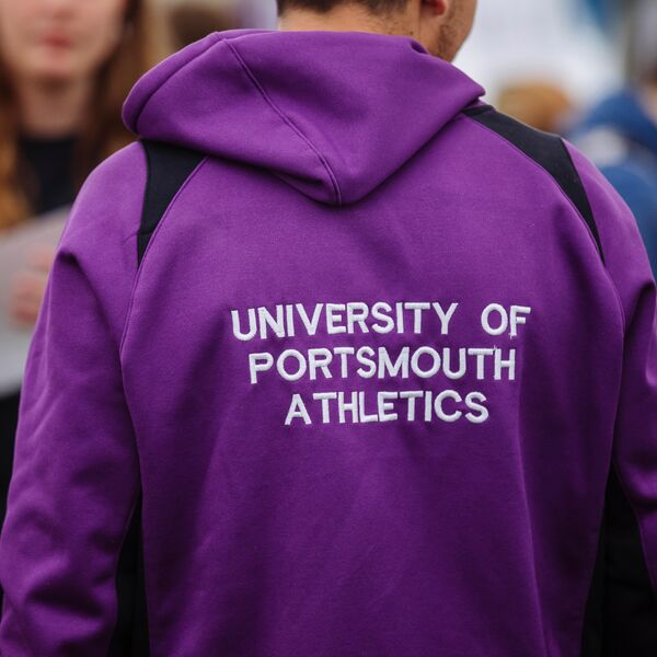 The back of a person wearing a University of Portsmouth Athletics club, purple jumper