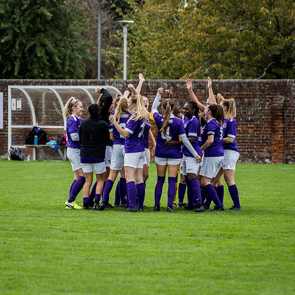 Women's football team wearing purple kit and celebrating