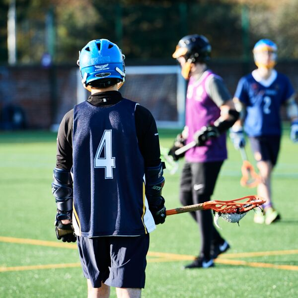 Lacrosse players during a match, the back of one player wearing a blue number four bib and holding lacrosse stick