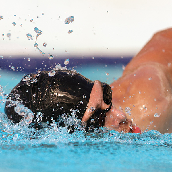 Swimmer wearing black cap and goggles, performing front crawl