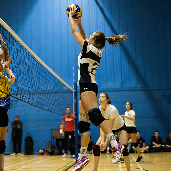 Volleyball player jumping in the air to hit the ball over the net