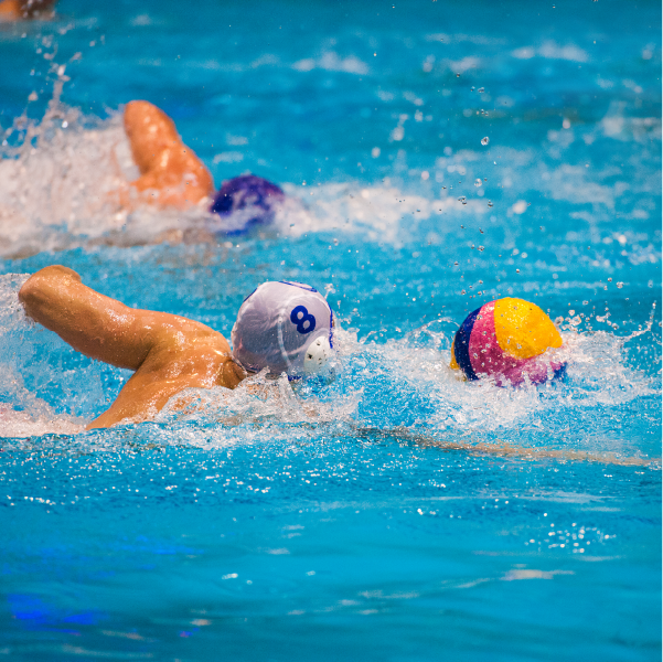Water polo player swimming for ball
