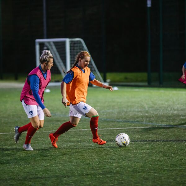 women wearing coloured bibs chasing after football during a match