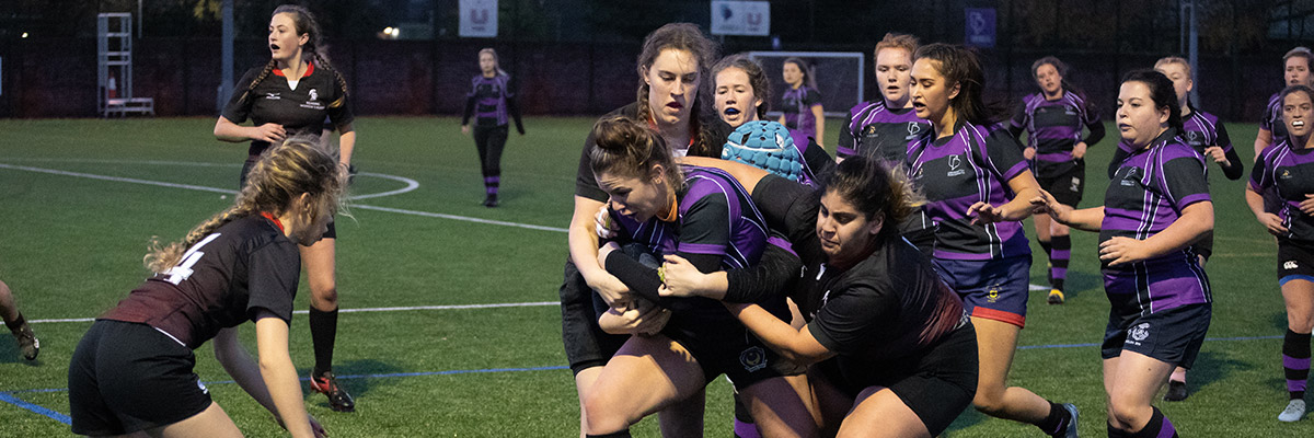players going in to tackle during women's rugby match