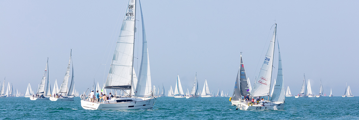 Lots of yachts with white sails sailing in a race on the solent