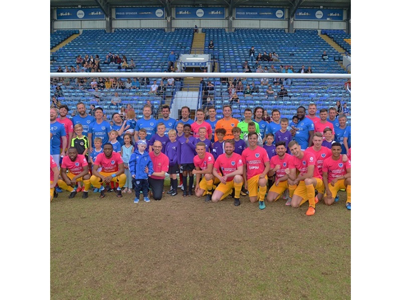 Footballers in the staff v students charity match pose on pitch