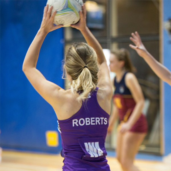 back of netball player with her arms raised about to pass the ball