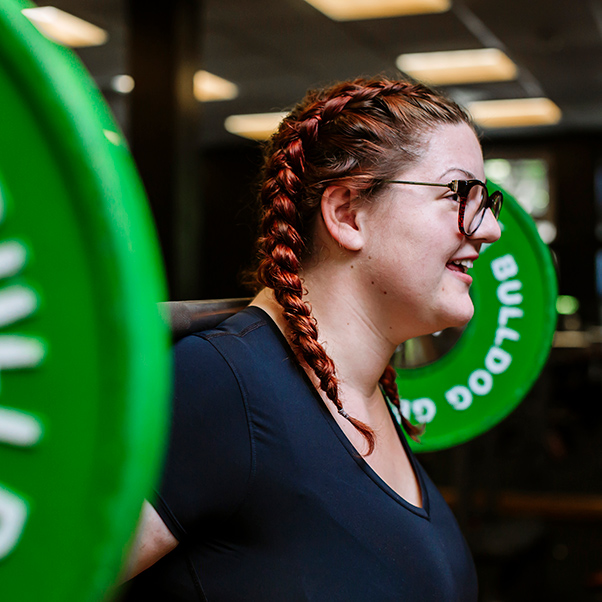 Woman with hair in plaits and wearing glasses, squatting barbell with green weights