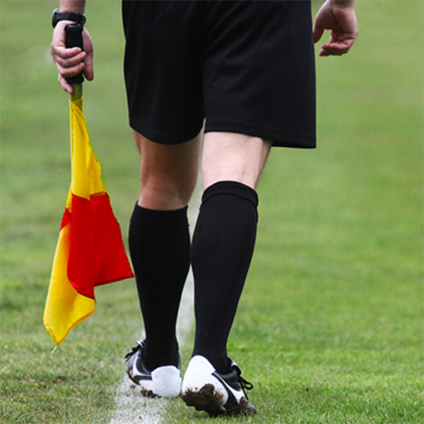 behind referee who is wearing long socks and holding red and yellow flag