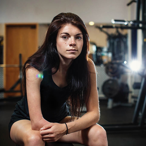 Lauren Steadman sat on a bench in the gym, leaning forward resting her arms on her legs