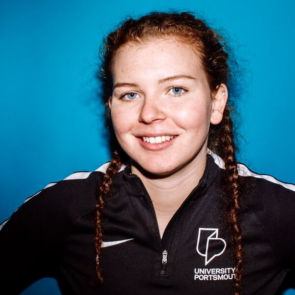 Sport scholar bobbie haywood wearing hair in plaits and Uop black sports kit, smiling for a photo