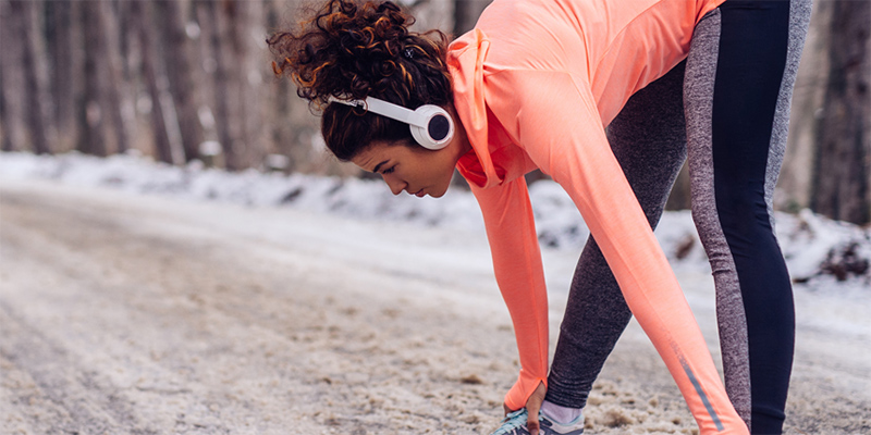 Woman, wearing running gear and headphones, bending forward stretching on a road covered with snow