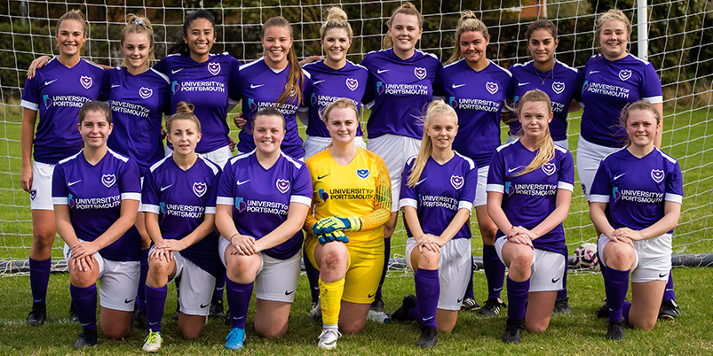 Women's football team kneeling for photograph in their purple UoP kit before their match