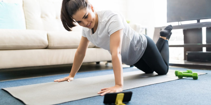 Woman exercising with phone in living room