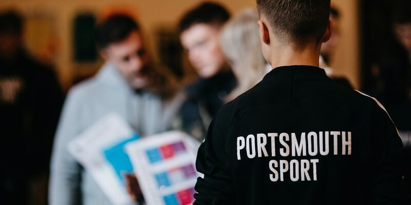Back of sport assistant wearing a black Portsmouth Sport jumper, supporting an open day