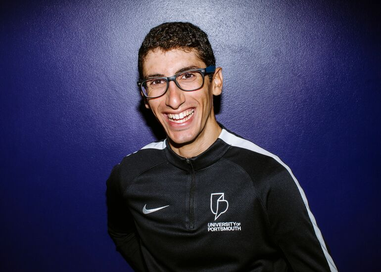 Alexandros wearing glasses, smiling and standing in front of a purple background