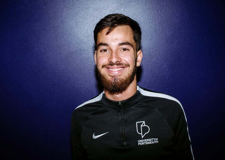 Pablo smiling in front of a dark purple wall