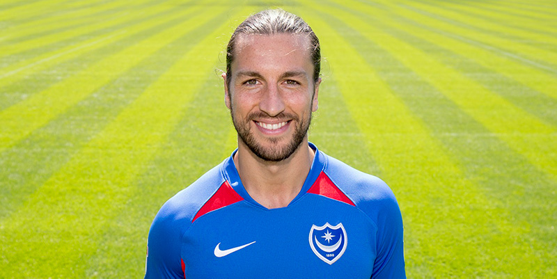 Christian Burgess smiling on green field wearing blue Portsmouth Football club kit